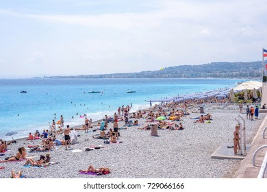 NICE, FRANCE - JUNE 27, 2017: Beautiful daylight view to famous beach. Blue water with people walking on sand.