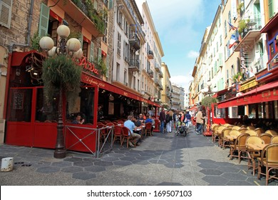 NICE, FRANCE - MAY 14, 2013: Narrow pedestrian street in Old Town of Nice, France with sidewalk cafes, souvenir shops and tourists walking around.