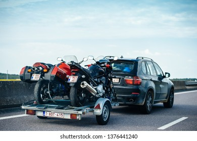 Nice, France - May 7, 2016: Rear view of Modern BMW SUV X5 driving fast on French highway with trailer holding two fast motorcycles for motocross