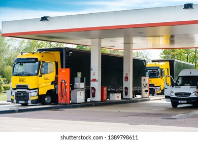 Nice, France - May 7, 2016: Two new modern Renault T520 Yellow Truck from the Formula One Sport Team at Total French gas station carrying the fast turbocharged Renault F1 Grand Prix