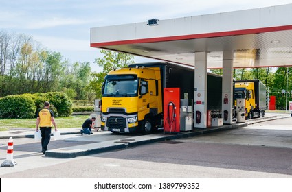 Nice, France - May 7, 2016: Wide image of two driver near new modern Renault T520 Yellow Truck from the Formula One Sport Team at Total French gas station