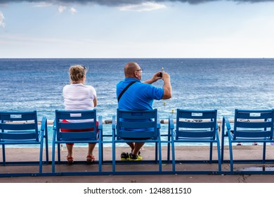 Nice, France - October 1, 2018: Couple relaxing on public bench and photograp sea view at Mediterranean sea of Nice, France on sunny day.