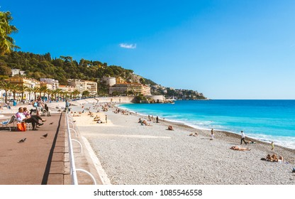 NICE, FRANCE - OCTOBER 13, 2009: Bright turquoise sea, blue sky and people relaxing on beach that stretches along Promenade des Anglais in Nice