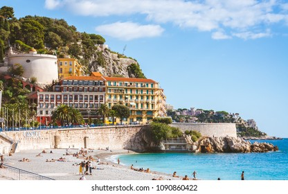 NICE, FRANCE - OCTOBER 13, 2009: Beautiful nicoise architecture and people relaxing on beach that stretches along Promenade des Anglais in Nice