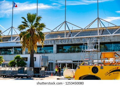Nice, France - October 3, 2018: View to the reception building of Nice airport in France. In the foreground you can see workers and various vehicles of the airport.