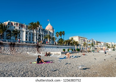 Nice, France - October 4, 2018: View over the beach of Nice, France, with bathers. In the background you can see the higher promenade with hotels.
