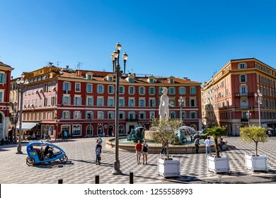 Nice, France - October 4, 2018: Street scene with a fountain, a bike taxi and historic buildings at Place Masséna in Nice, France.
