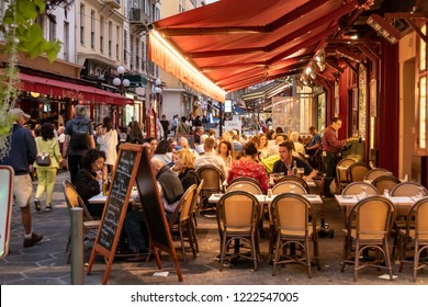 Nice, France - October 5, 2018: Guests in a restaurant with tables and chairs on the sidewalk at a street in Nice, France, in the dusk.