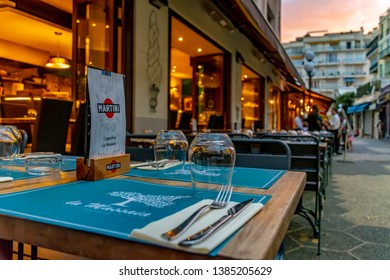 Nice, France - October 5, 2018: Evening shot of a small restaurant with chairs and laid tables on the sidewalk of a street in Nice, France.