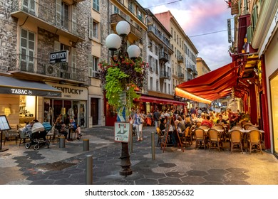 Nice, France - October 5, 2018: Evening shot of shops and a restaurant with tables, chairs and people on the sidewalk of a street in Nice, France.