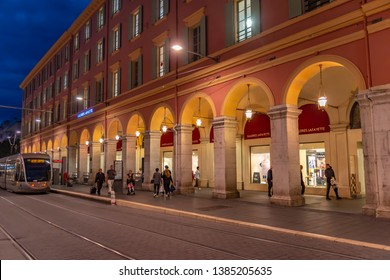 Nice, France - October 5, 2018: Scene on a evening in Nice in front of the department store Galeries Lafayette with strolling people and a tram.