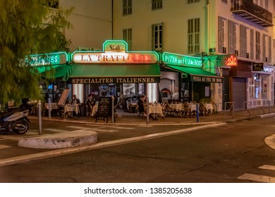 Nice, France - October 5, 2018: Evening shot of a small restaurant with tables, chairs and people on the sidewalk of a street in Nice, France.