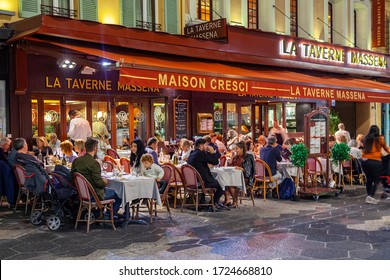 Nice, France, October 8, 2019. People have rest and eating in a traditional street cafe on a picturesque street in the evening