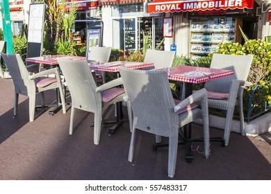 NICE, FRANCE, on January 5, 2017. Little tables of street cafe under the open sky on Angliyskaya Embankment (fr. Promenade des Anglais)