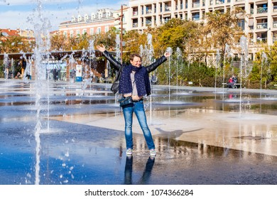 NICE, FRANCE, on March 6, 2018. The attractive woman poses against the background of the fountain in the La promenade du Paillon park