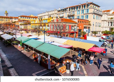 NICE, FRANCE, on March 7, 2018. The well-known Cours Saleya market in the old city. Counters with vegetables, fruit and farmer production are located under striped awnings