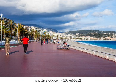 NICE, FRANCE, on March 7, 2018. A view of historical Promenade des Anglais, one of the most beautiful in a pattern lit with the sunset sun. People walk along the sea