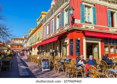 NICE, FRANCE, on March 7, 2018. People have a rest and eat in picturesque street cafe in a historical part of the city.