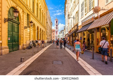 NICE, FRANCE - SEPTEMBER 02, 2015: People walking on narrow street in old tourist part of Nice - fifth most populous and one of most visited cities in France, receiving 4 million tourists annually.