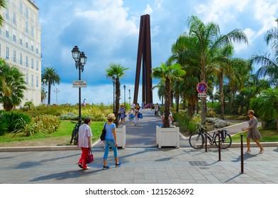 NICE, FRANCE - SEPTEMBER 15, 2018: Unknown people walk to Obelisk de Venet, or Nine Oblique Lines (Neuf Lignes Obliques) on Promenade des Anglais, Nice, France