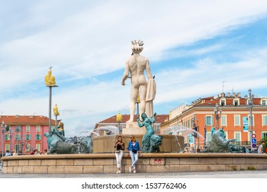 Nice, France - September 17 2019: Two women relax in front of the Apollo Statue at the Fountain of the Sun in Place Massena, in the city of Nice France, on the French Riviera.