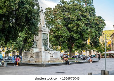 Nice, France - September 23 2019: Local French men and women relax at the water fountain and statue in Place Garibaldi in central Nice, France, on the French Riviera