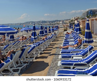 Nice, France - September 27, 2017: Blue Umbrellas and deck chairs on the Beach at Nice France