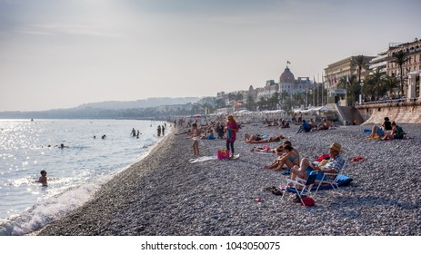 NICE, FRANCE - SEPTEMBER 29, 2017: People relaxing on the public beach in Nice, France, near the Promenade des Anglais.