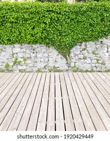 Nice garden terrace with overgrown wall and wooden floor.