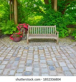 Schöne Gartenterrasse mit Parkbank und Steinparkplatz
