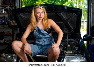 nice girl auto mechanic in the garage on a broken car