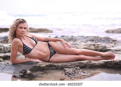 Nice girl in bikini lying on a seaside rock