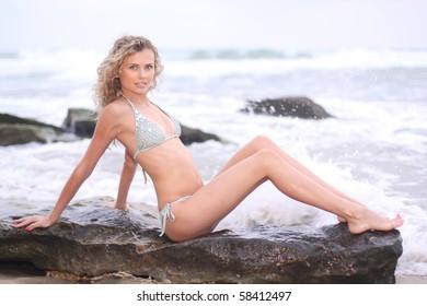 Nice girl in bikini sitting on a seaside rock