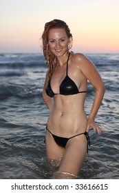 Nice girl in a black bikini coming out from sea on sunset