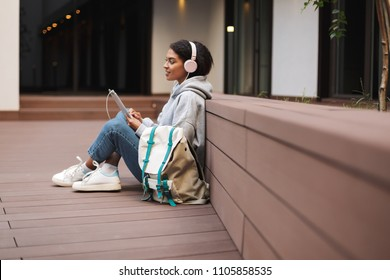 Nice girl with dark curly hair in headphones sitting on floor with tablet in hands and big backpack near while spending time in courtyard of university