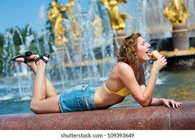 Nice girl enjoys the ice cream. Fountain in background.