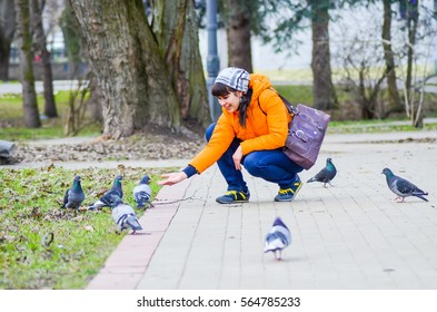 Nice girl feed the pigeons from hands in park.