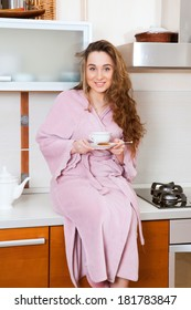 the nice girl in a gown with a Cup of tea sitting in the kitchen