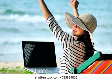 Nice girl with hat sitting chair on the beach raised her hands and using laptop  while relaxing, woman using laptop on holiday and sitting on the beach with raised arms while feeling happy