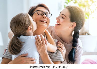 A nice girl, her mother and grandmother enjoy sunny morning. Good time at home. Family playing in the bedroom.