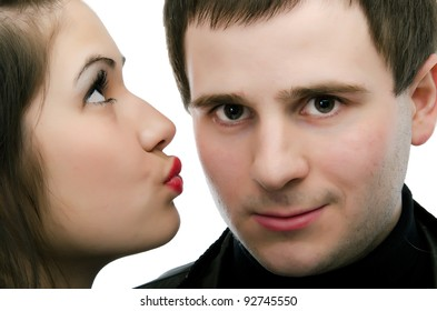 Nice girl kisses the young modest guy on a cheek. gradient gray