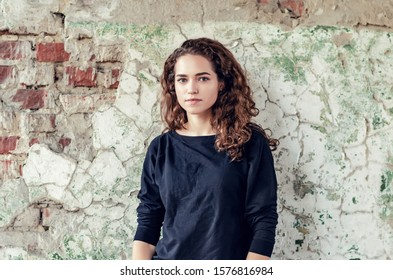 Nice girl, portrait in pastel colors on background of old painted wall. Perfect smile on face, curly hair.