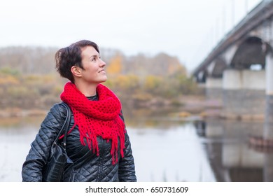 Nice girl in red scarf outdoor in autumn day