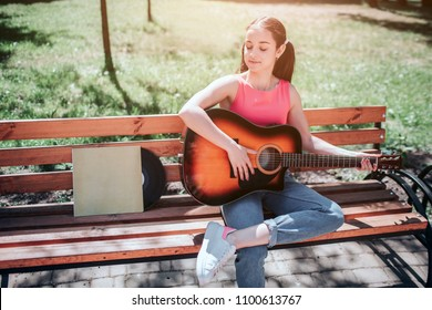 Nice girl is sitting on bench and playing the guitar. She is looking down to the vynil and its cover that is on bench as well. She is enjoying the moment.