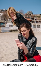 a nice girl with a straight dark hair sits on the sand on the beach and looks into the iPhone and a girl with curly blond hair stands and holds her hand near the face