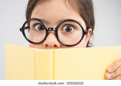 nice girl surprised and wearing glasses. little girl holding yellow book