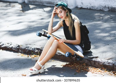 Nice girl, wearing in cap, shirt, sandals and shorts, with backpack, sitting on the pavement and holding skateboard on her knees, on the street, full body