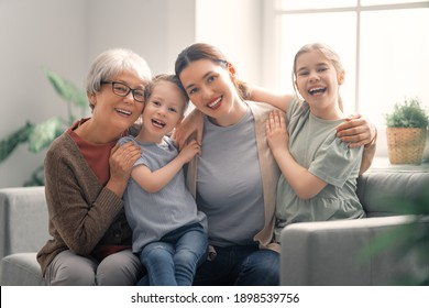 A nice girls, their mother and grandmother are hugging and  enjoying spending time together at home.