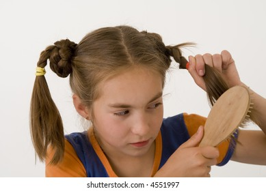 The nice girl-teenager comb one's hair .