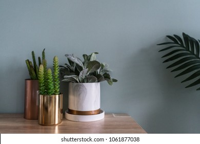 Nice gold mirror vase and copper pots with artificial plant decor on green background setting on wood table/interior detail /DIY design/copy space